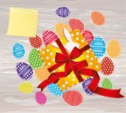 Multicolored easter eggs with pattern. Yellow sheet of paper for. Notes. Sticker.A box with a gift tied with a red ribbon and a bow. An empty space for an ad stock illustration