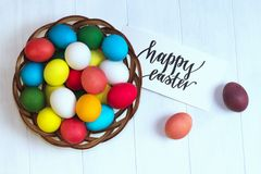 Multicolored easter eggs in a wicker basket on wooden white background, black inscription Happy Easter. Multicolored easter eggs in a wicker basket on a wooden Stock Photography