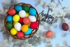 Multicolored easter eggs in a wicker basket on a wooden white background, inscription Happy Easter. Multicolored easter eggs in a wicker basket on a wooden white Royalty Free Stock Photography