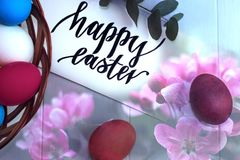 Multicolored easter eggs in a wicker basket on a wooden white background, inscription Happy Easter. Multicolored easter eggs in a wicker basket on a wooden white Stock Photos