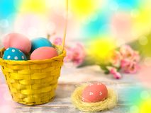 Multicolored Easter eggs in a woven straw basket, ribbon on a wooden background. Country style. Copy spase Royalty Free Stock Photo