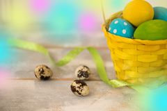 Multicolored Easter eggs in a woven straw basket, ribbon on a wooden background. Country style. Copy spase Royalty Free Stock Images