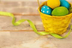 Multicolored Easter eggs in a woven straw basket, ribbon on a wooden background. Country style. Copy spase Royalty Free Stock Image