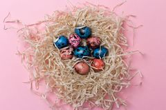 Close up quail easter eggs in nest at pink background stock images