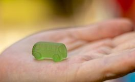 Multicolored edible cars from marmalade on a children`s palm. Business idea for obtaining a mortgage or bank credit loan. Assistance to transport. Trust your stock photography