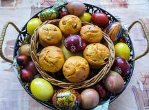 Multicolored eggs, boiled and painted by hand, and small cupcakes cooked for Easter stock photos
