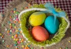 Multicolored eggs in easter festive basket on canvas napkin stock photos