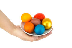 Multicolored eggs and golden lie on a ladle in a ceramic saucer on a white. Background Stock Photography