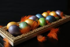 Multicolored eggs painted for Easter lie on a golden tray. Feathers, easter, paint eggs, decorate eggs.black background Stock Photography