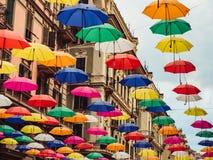 Multicolored en heldere paraplu's die tussen huizen hangen stock afbeelding