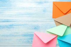 multicolored enveloppen en op een blauwe houten lijst Vrije ruimte Plaats voor tekst Hoogste mening royalty-vrije stock foto