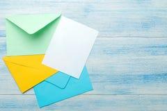 Multicolored enveloppen met een spatie voor de tekst op een blauwe houten lijst Hoogste mening royalty-vrije stock foto's