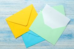 Multicolored enveloppen met een spatie voor de tekst op een blauwe houten lijst Hoogste mening stock afbeeldingen