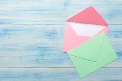 Multicolored enveloppen met een spatie voor de tekst op een blauwe houten lijst Hoogste mening royalty-vrije stock foto