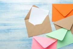 Multicolored enveloppen met een spatie voor de tekst op een blauwe houten lijst Hoogste mening stock foto's