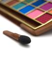 Multicolored eye shadows and brush. Multicolored eye shadows with cosmetics brush isolated on a white background Royalty Free Stock Photography