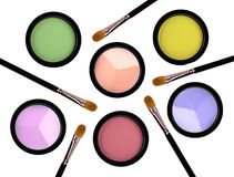 Multicolored eye shadows and brushes isolated on white backgroun Stock Images