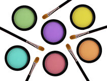 Multicolored eye shadows and brushes isolated on white Stock Photography