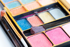 Multicolored eye shadows and cosmetics brush Royalty Free Stock Images