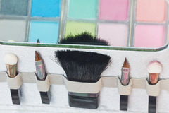 Multicolored eye shadows and cosmetics brush Stock Images