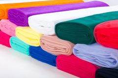 Multicolored fabric in rolls. Tulle. neatly stacked in a row
