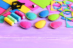 Multicolored felt Easter eggs crafts, felt sheets and scraps, scissors, thread set, thimble on a table. Simple Easter sewing craft Royalty Free Stock Photos