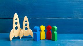 Multicolored figures of people are standing near missiles. The international scientific community. Cooperation and joint development of space technologies and royalty free stock photo
