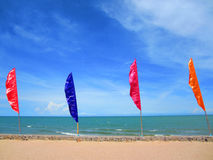 Multicolored flag on the beach with blue sky. Royalty Free Stock Images