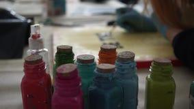Multicolored flessen van verf De meisjeskunstenaar trekt brieven op de kleurenraad stock videobeelden