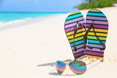 Multicolored flip-flops and sunglasses on a sunny beach of Seych Royalty Free Stock Photography