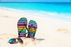 Multicolored flip-flops and sunglasses on a sunny beach.Tropica Stock Photos