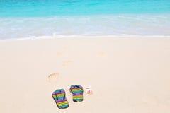 Multicolored flip-flops on a sunny beach.Tropical beach vacatio Stock Image