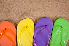 Multicolored flipflops in the sand. Orange, yellow, blue and green flipflops in sand stock photo