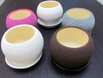 Multicolored flower pots, round shape on the table stock images