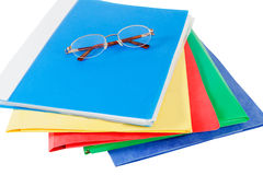 Multicolored folders with glasses on white background Stock Photo