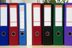 Multicolored folders standing on a shelf Stock Images