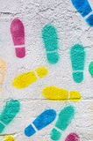 Multicolored footprints in a white wall Stock Image