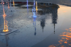 Multicolored fountain and reflection of the church and clouds. K Royalty Free Stock Images