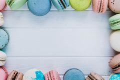 Multicolored frame from macaroons or macaron on a white wooden background, almond cookies in the form of decoration. Copy space Royalty Free Stock Photos