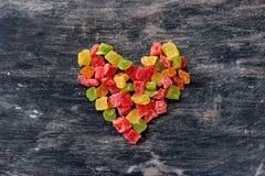 Multicolored fruit geglaceerd in de vorm van hart op een donkere houten uitstekende achtergrond Stock Foto's