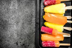Multicolored fruit ice made from fruits. On a rustic background Royalty Free Stock Images