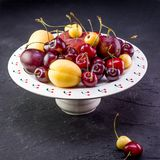 Multicolored fruits. Fresh peaches and cherries on aceramick plate. Red and yellow fruits, fresh peaches, plums and cherries on a white kermic board and dark Royalty Free Stock Photography