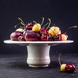 Multicolored fruits. Fresh peaches and cherries on aceramick plate. Red and yellow fruits, fresh peaches, plums and cherries on a white kermic board and dark Royalty Free Stock Images
