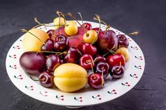 Multicolored fruits. Fresh peaches and cherries on aceramick plate stock photos