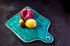 Multicolored fruits. Fresh peaches and cherries on a ceramic board. Red and yellow fruits, peaches, plums and cherries on a green ceramic board on a dark Stock Photo