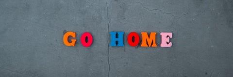 Multicolored gaat, wordt het huiswoord gemaakt van houten brieven op een grijze gepleisterde muurachtergrond stock foto