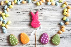 Multicolored gingerbread cookies in the shape of bunnies and decorated eggs on a white wooden textural background. Homemade ginger. Bread, easter concept Easter stock images