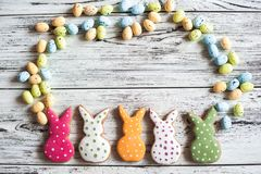 Multicolored gingerbread cookies in the shape of bunnies and decorated eggs on a white wooden textural background. Homemade ginger. Bread, easter concept Easter royalty free stock photos