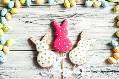 Multicolored gingerbread cookies in the shape of bunnies and decorated eggs on a white wooden textural background. Homemade ginger. Bread, easter concept Easter royalty free stock photo