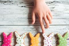 Multicolored gingerbread cookies in the shape of bunnies and decorated eggs on a white wooden textural background. Kids hands hold. Ing homemade gingerbread royalty free stock photos